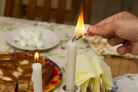 familia orando: Una mujer enciende una vela de shabat