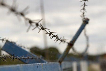 Security with a barbed wire fence Stock Photo