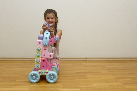 Seven-year-old girl playing with toys in the room