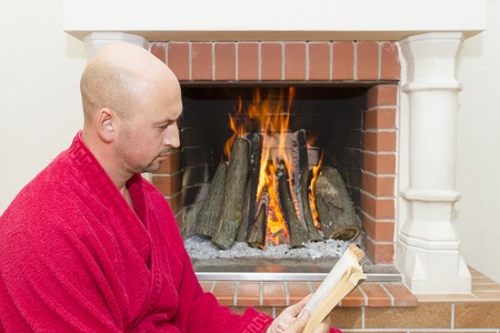 cute guy: young man reading a book near the fireplace