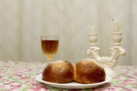shabat: Velas de Shabat en candelabros de vidrio con fondo cubierto de jalá borrosa. Foto de archivo