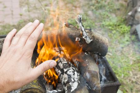 man warming his hand by a fire. Poor men warm outdoors near smoking barrel