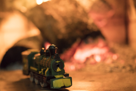Model of a green train against a background of blurred lights