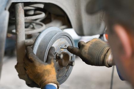 Close-up repair drum brake of car wheel in garage. Archivio Fotografico