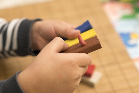 Childrens hands hold the clay of different colors