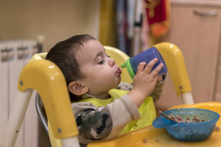Baby boy drinks from a drinker Banco de Imagens