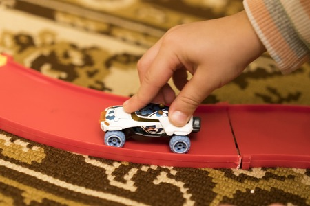 game drive: Childs hand holding a toy car.