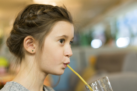 Cute little girl drinks from the straw Stock Photo
