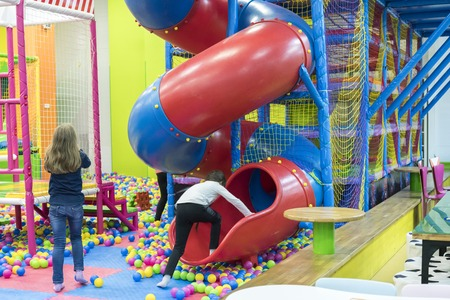 Children on a large colorful playground inside the room