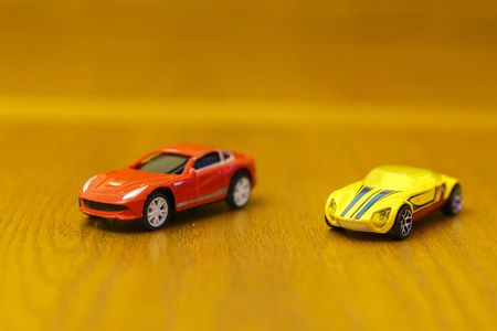 Toy cars red and yellow on a wooden background Stock Photo