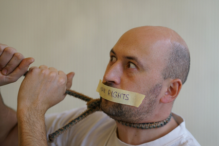 Man with a sealed mouth pulled on a rope