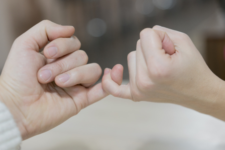 Man and woman making a pinkie promise.