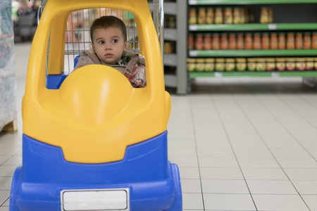 Toddler boy in a cart in the supermarket