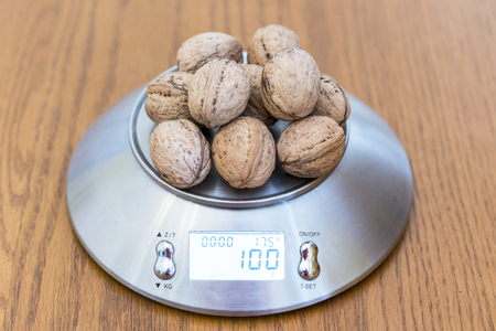 One hundred grams of walnuts on the scales Imagens