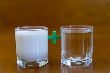 A glass of milk + a glass of water on a brown background Stock Photo