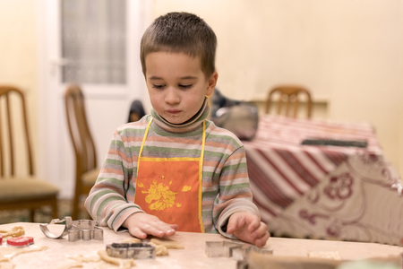 little boy 4 years old in an orange apron molding dough cookies