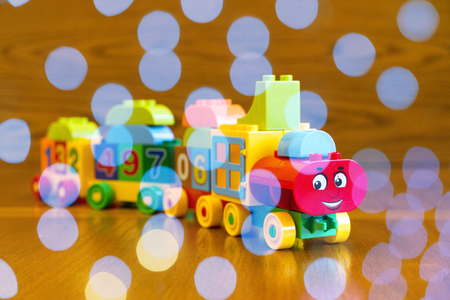 Childrens locomotive with wagons, blue bokeh