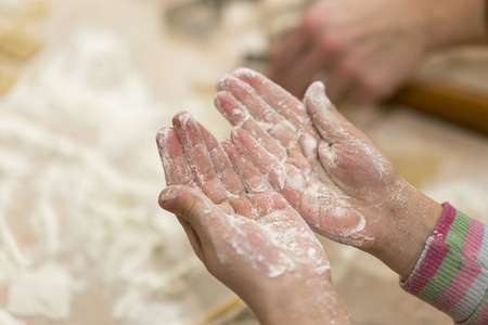Baby hands in flour. rolls out the dough