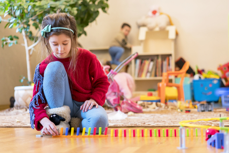 Girl 8 years old is played in the room with toys