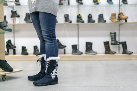 A woman trying on spring boots in a shoe store Imagens