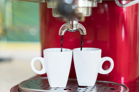 Red coffee machine pours two espresso under the rays of the morning sun.