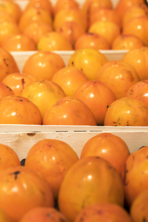 Ripe persimmon in wooden boxes. close-up.