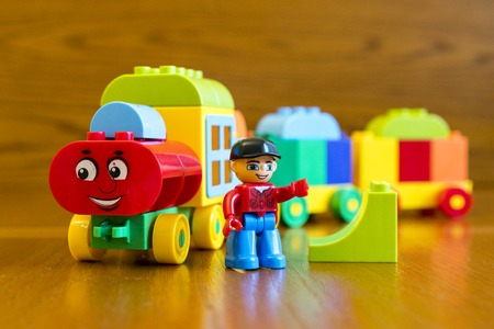 Childrens locomotive with wagons, on a wooden background