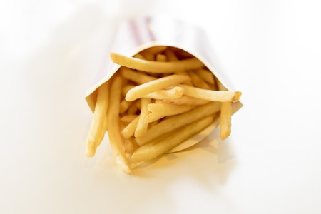French fries in a box on a light background. Unhealthy food. Delicious food.