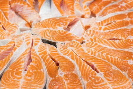 Salmon Red Fish Steak at the fish market. Raw fresh steaks of Salmon fish as background. Large Pile of salmon steak with ice. Big organic steaks of salmon lined up for sale.