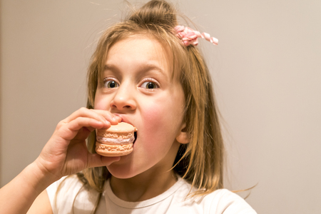 little girl biting a pink cake