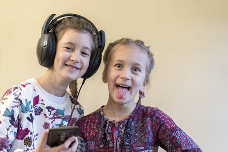 Two cheerful girls 5 and 7 years old listen to music on the smartphone.