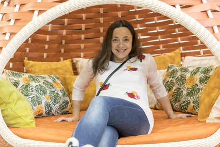 Young beautiful woman is resting in a summer gazebo.