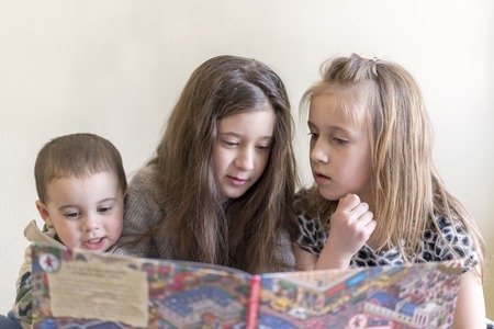 Three small children read a large book. Two sisters and a brother. Light background. European appearance.
