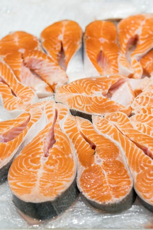 Salmon Red Fish Steak at the fish market. Raw fresh steaks of Salmon fish as background. Large Pile of salmon steak with ice. Big organic steaks of salmon lined up for sale