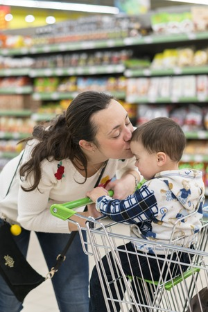 Happy mother embracing and kissing her son in the store.