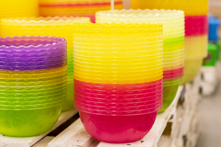 Plastic multi-colored bowls on the shelf in the store. Stock Photo