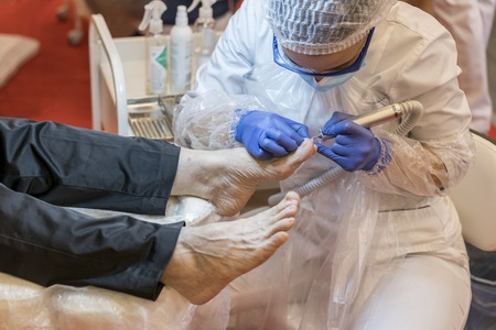 The process of pedicure in a professional beauty salon. Toned image. hardware processing of toes. Care of the skin of the feet close up view Standard-Bild