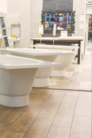 baths in the plumbing store. Sanitary engineering shop. White bathrooms. Stock Photo