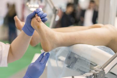 pretty doctor examining an elderly patient's foot.