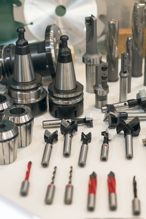 New saws and drills on the stand. New modern industrial drills and mills of the different sizes. Small depth of sharpness. Foto de archivo - 103430745