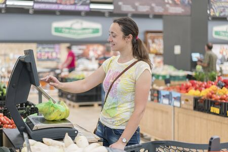 Young girl weighing banana in supermarket. Shopping. Woman weighting banana fruits bio food in vegetable store or supermarket.