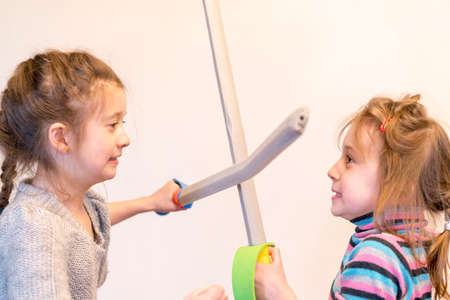 Two girls with toy swords play knights. Deyochki argue and get angry. conflict.