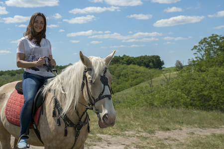 Photo of the small woman on a big horse in summer field. Image of happy female sitting on purebred horse and looking at camera outdoors