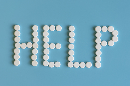 White pills on blue background word help. White medical pills on a blue background. Help word concept.