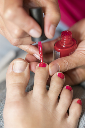 The master covers the customer's nails with varnish. Hands in gloves cares about a woman's foot nails. Pedicure, manicure beauty salon concept. Nail varnishing in red color 写真素材