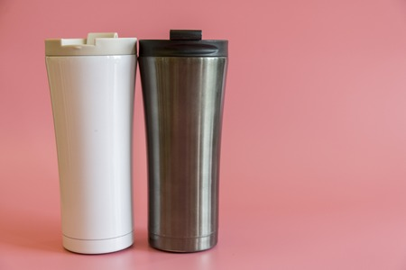 two insulated cups on a pink background