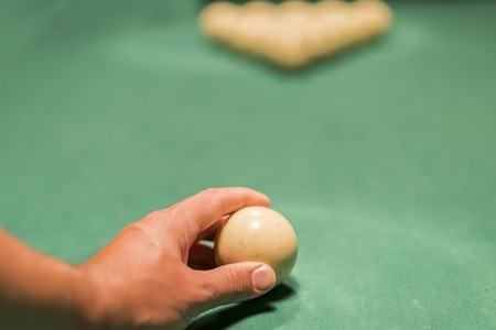 A mans hand puting a billiard ball. Preparation for the decisive blow. Stock Photo