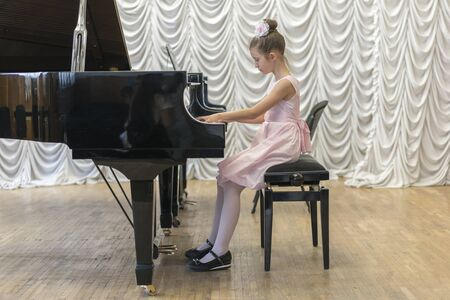 girl in a beautiful pink dress playing on a black grand piano. Girl playing on a black piano Stok Fotoğraf - 131848969