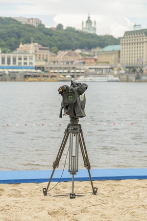 Television camera on the river beach. Lonely camcorder on a tripod. Vertical photo. Standard-Bild - 105137648