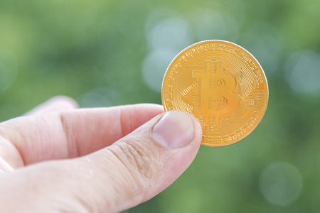 Golden bitcoin on grey background. Bitcoin is a modern way of exchange and this crypto currency is a convenient means of payment in the financial and web markets.